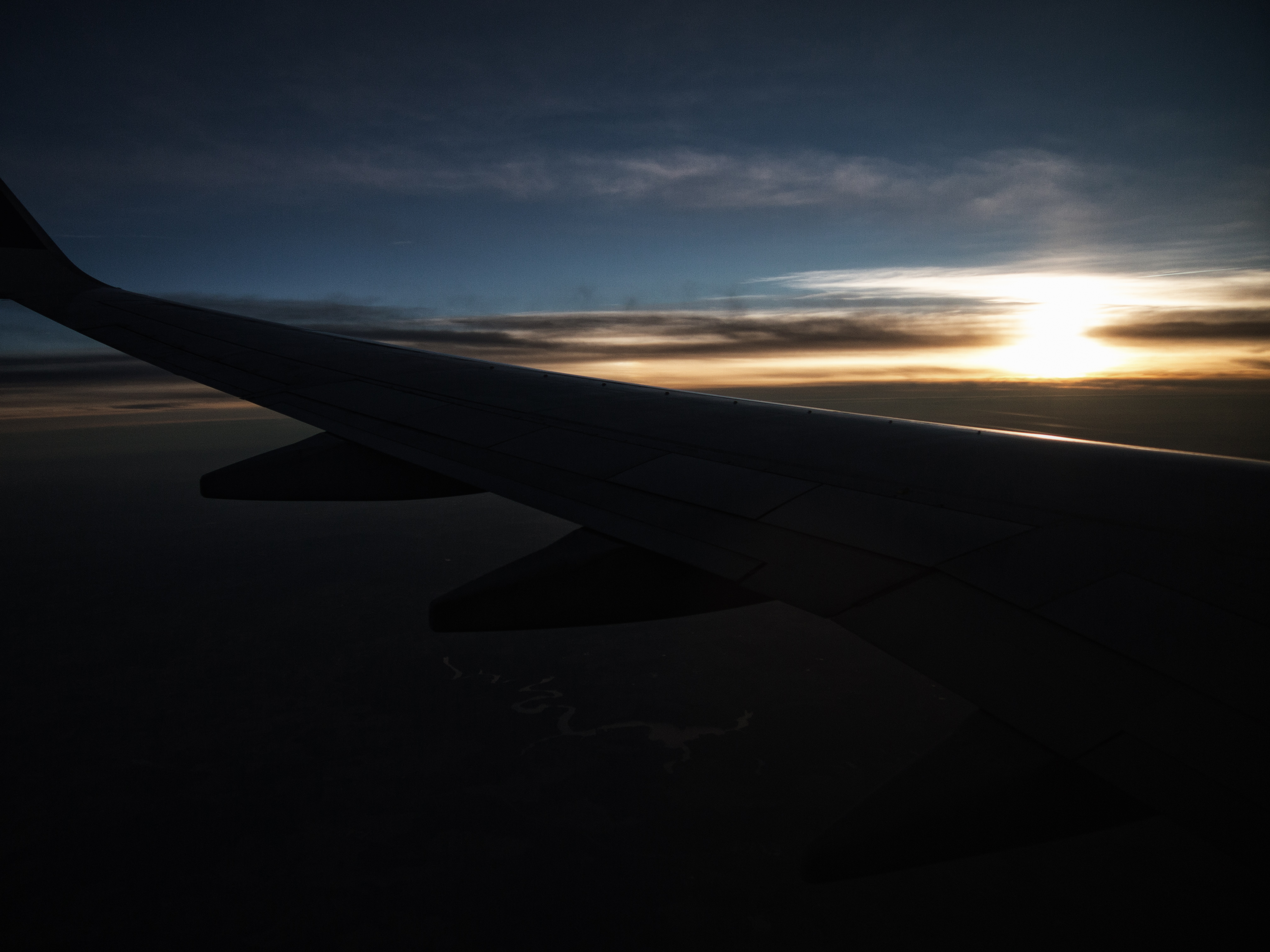 First time flying - Airplane wing at sunset